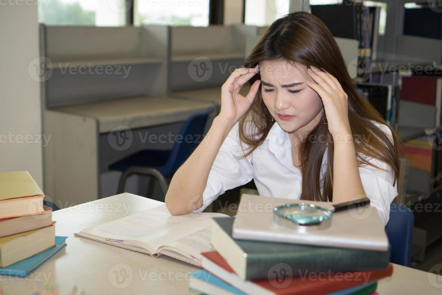 portret van student hoofd aan te raken tijdens het lezen van boek in universiteitsbibliotheek foto