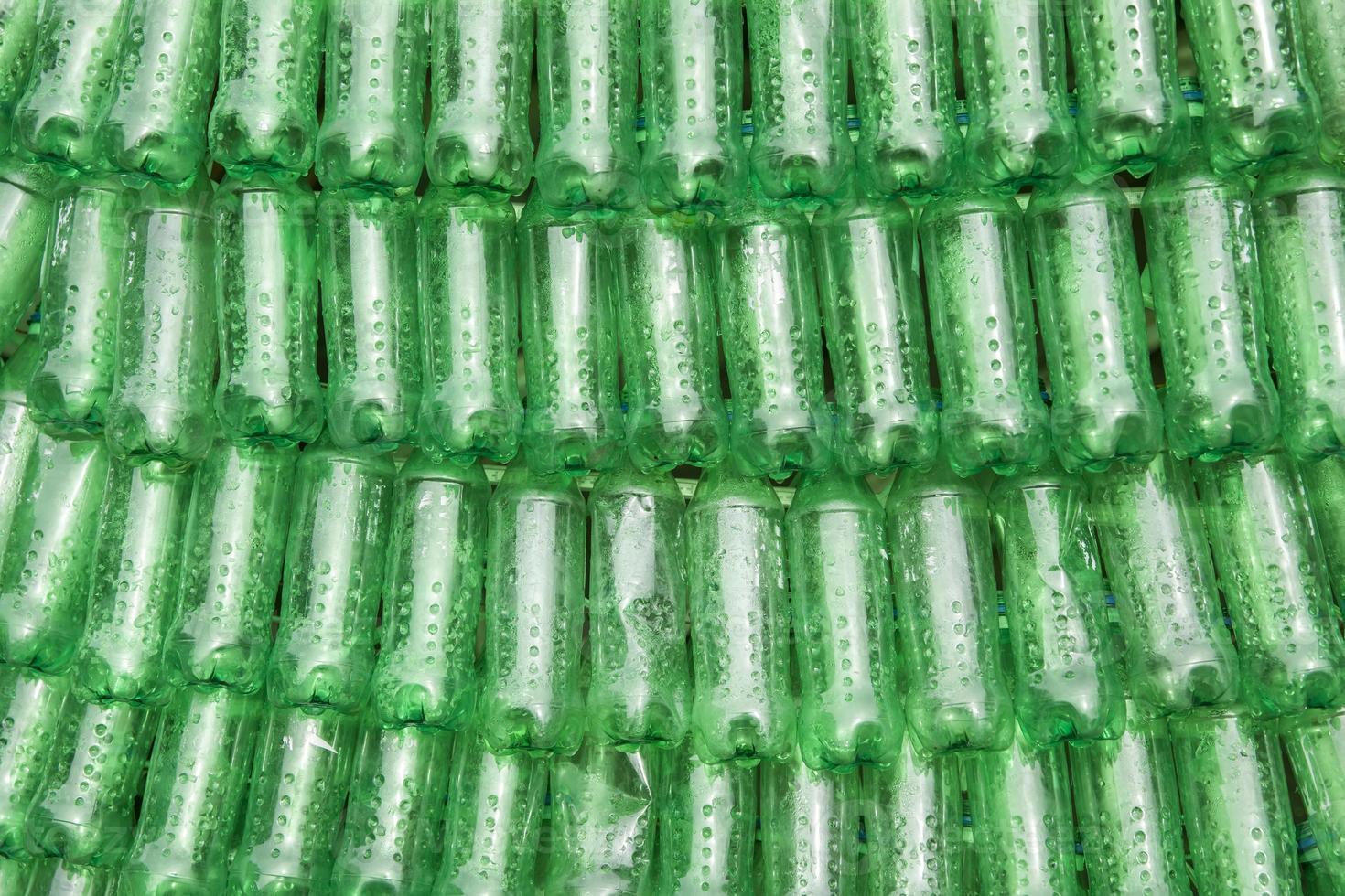 rijen groene plastic flessen naast elkaar gestapeld foto