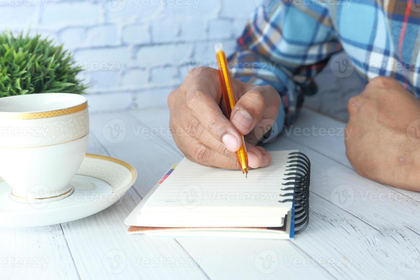 man schrijven op een notitieblok foto