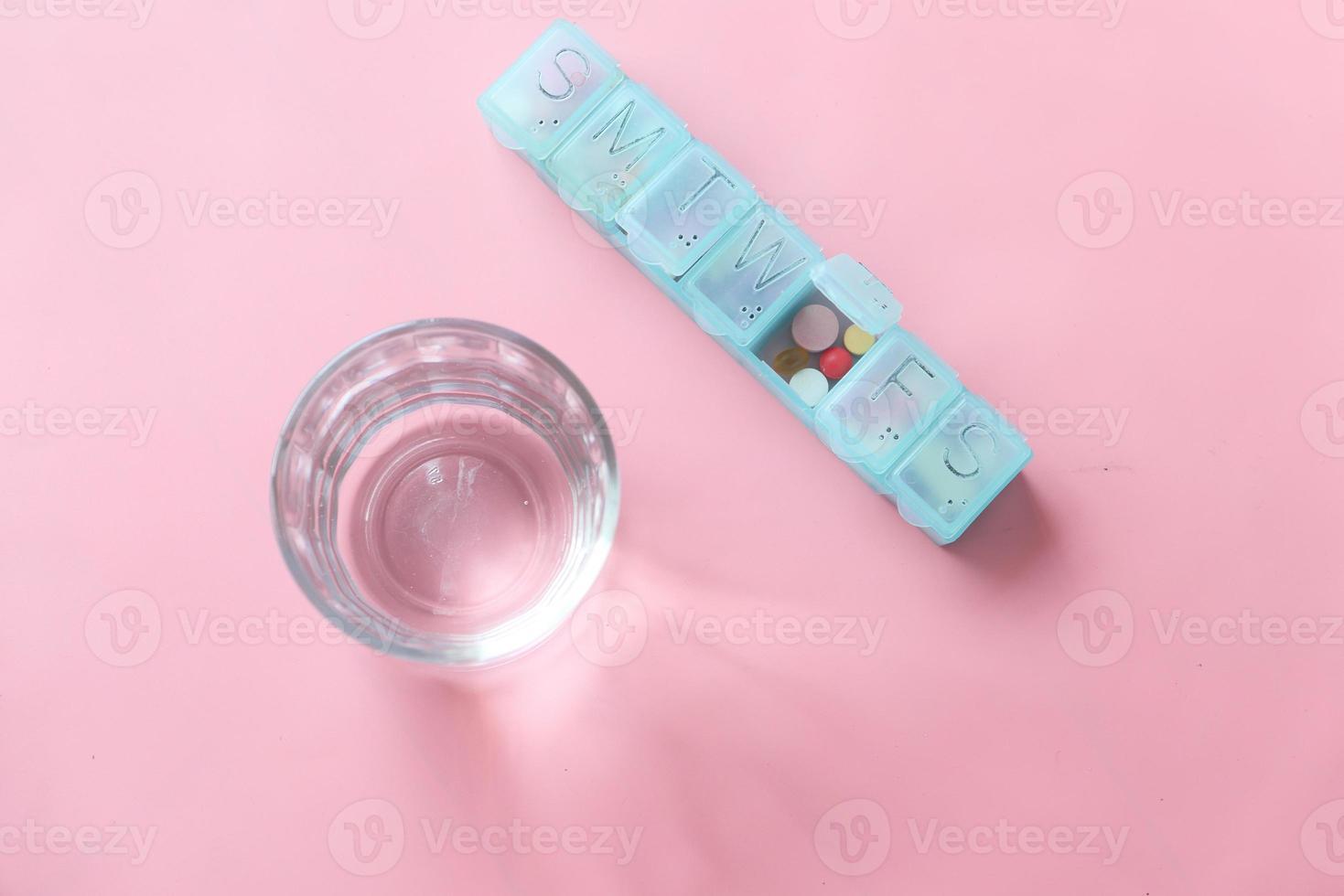 pillendoosje op roze achtergrond foto