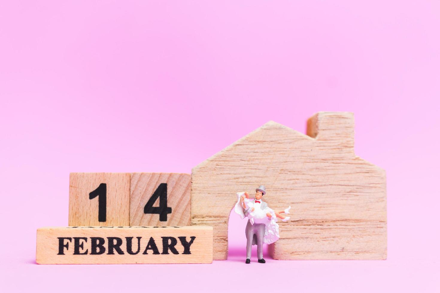 miniatuur bruiloft van een bruid en bruidegom paar op een roze achtergrond, Valentijnsdag concept foto