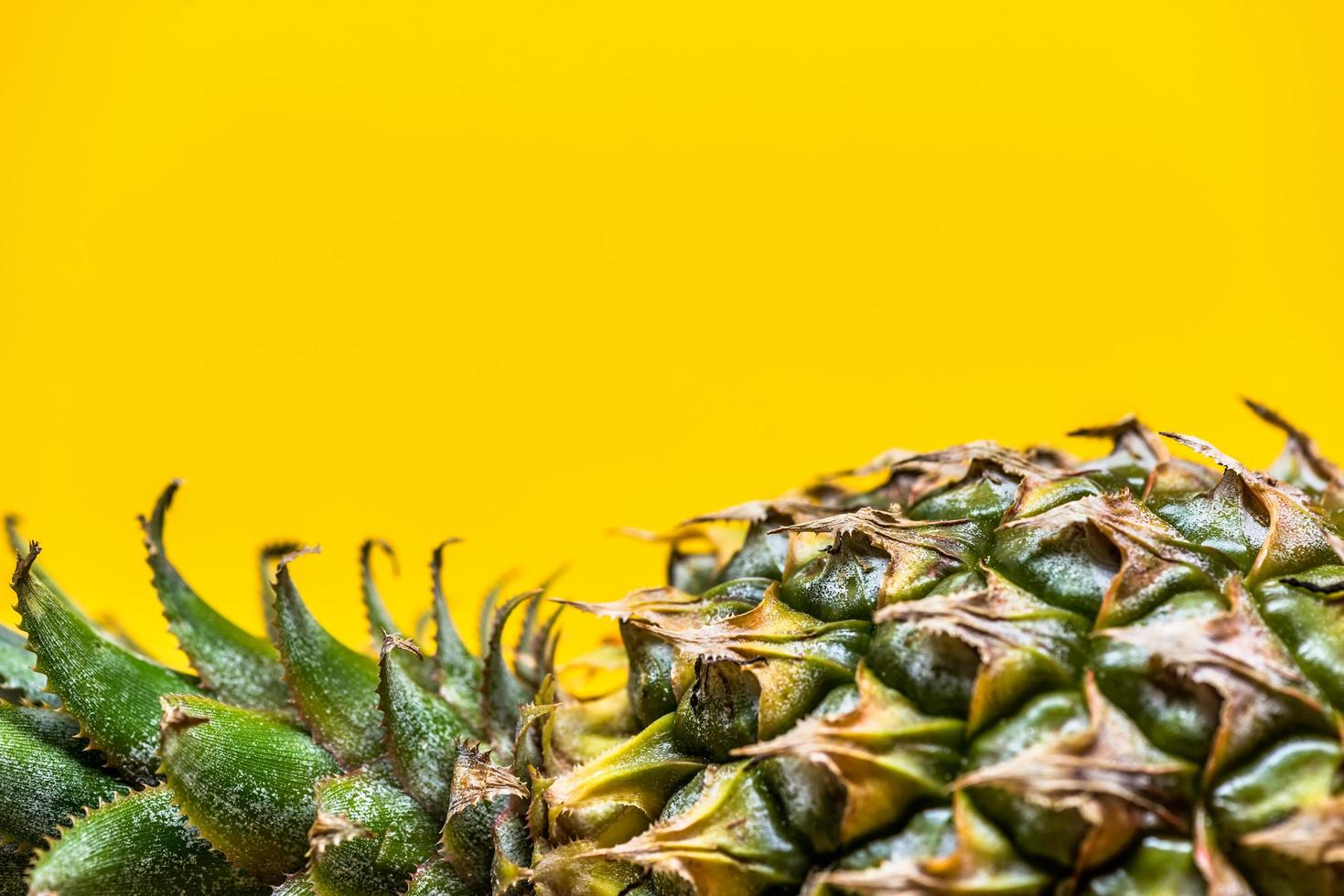 liggende ananas op eenvoudige gele achtergrond foto