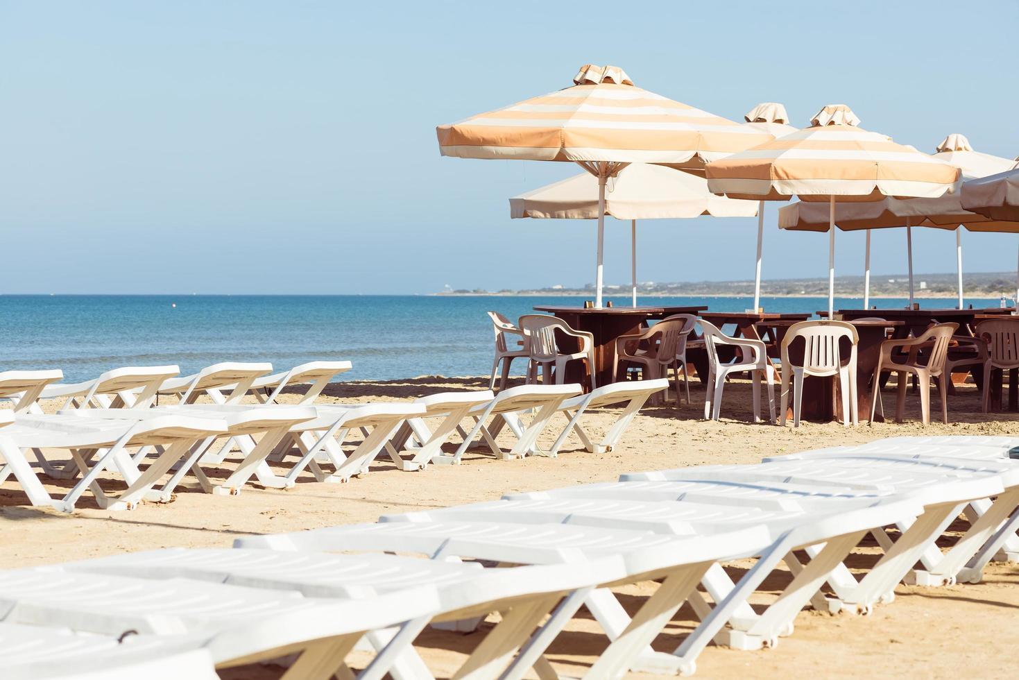 lege ligbedden en parasols op het strand foto