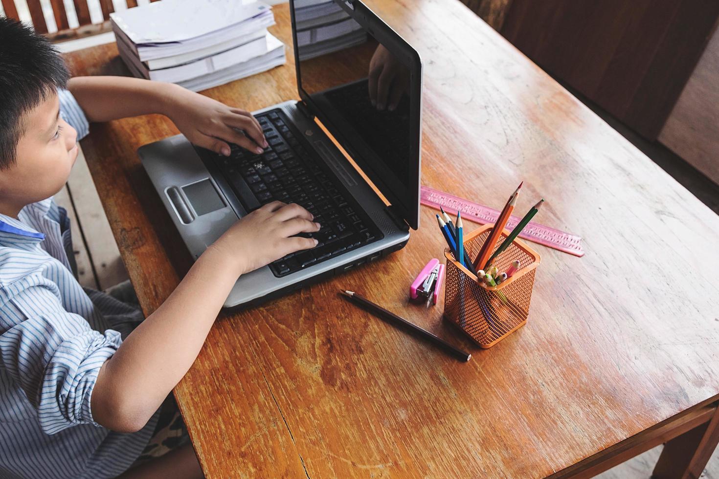 jongen die aan laptop naast kop van potloden op een houten bureau werkt foto