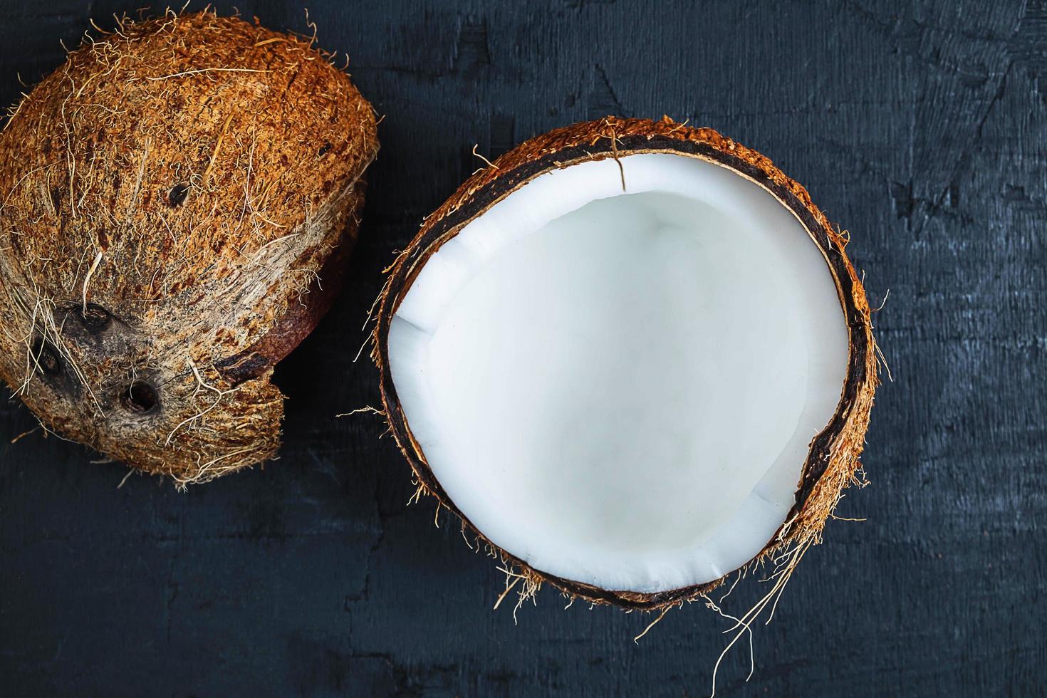 kokosnoot in tweeën gesneden op een zwarte tafel achtergrond foto