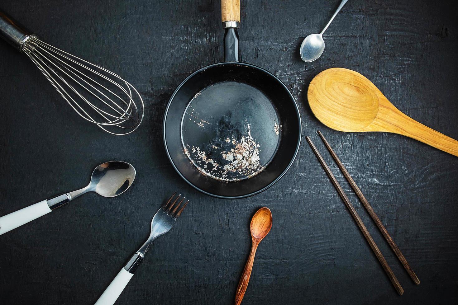 keukengerei en een zwarte koekenpan op zwarte lijstachtergrond foto