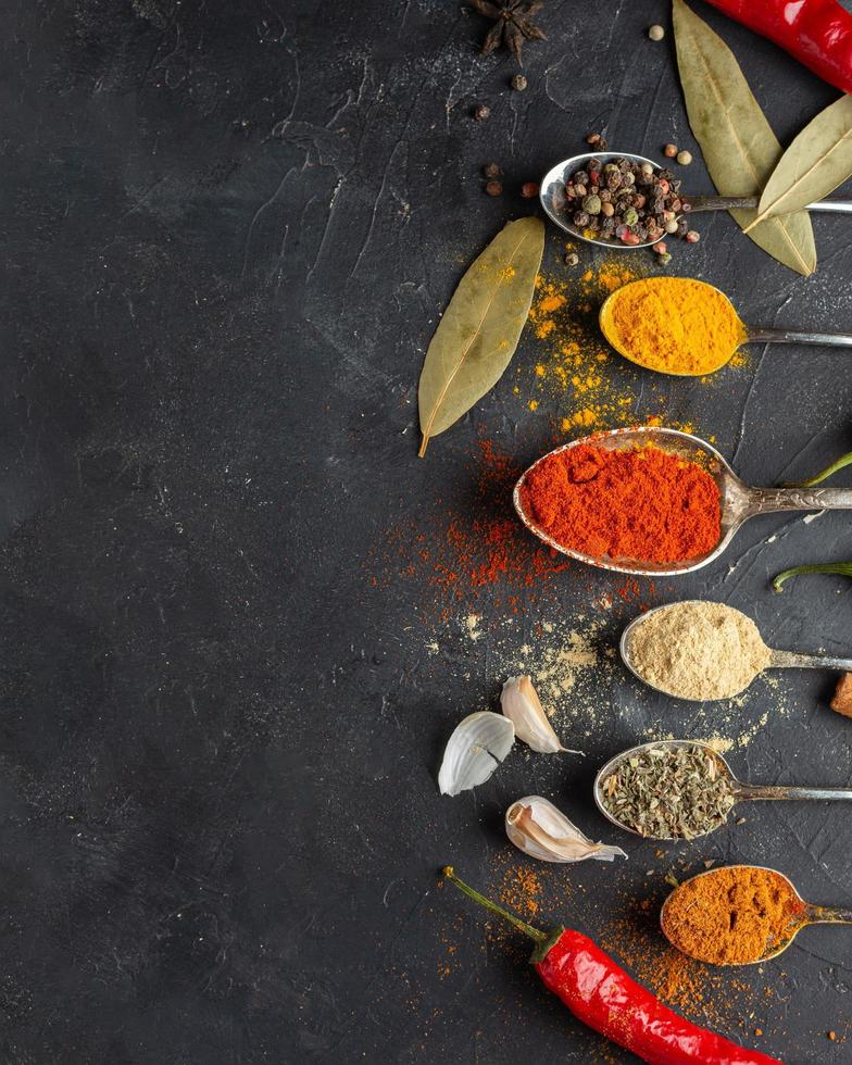 specerijen en kruiden in lepels op een donkere achtergrond foto