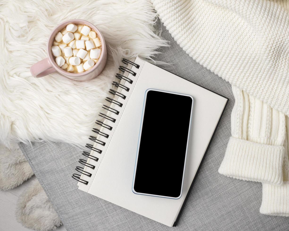 lege smartphone met warme chocolademelk foto