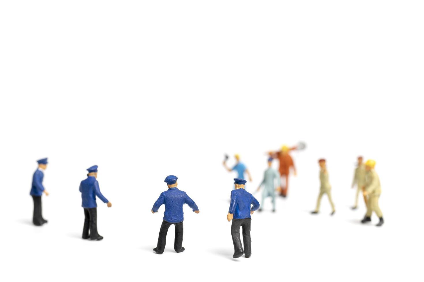 miniatuurpolitie en een boze menigte op een witte achtergrond foto