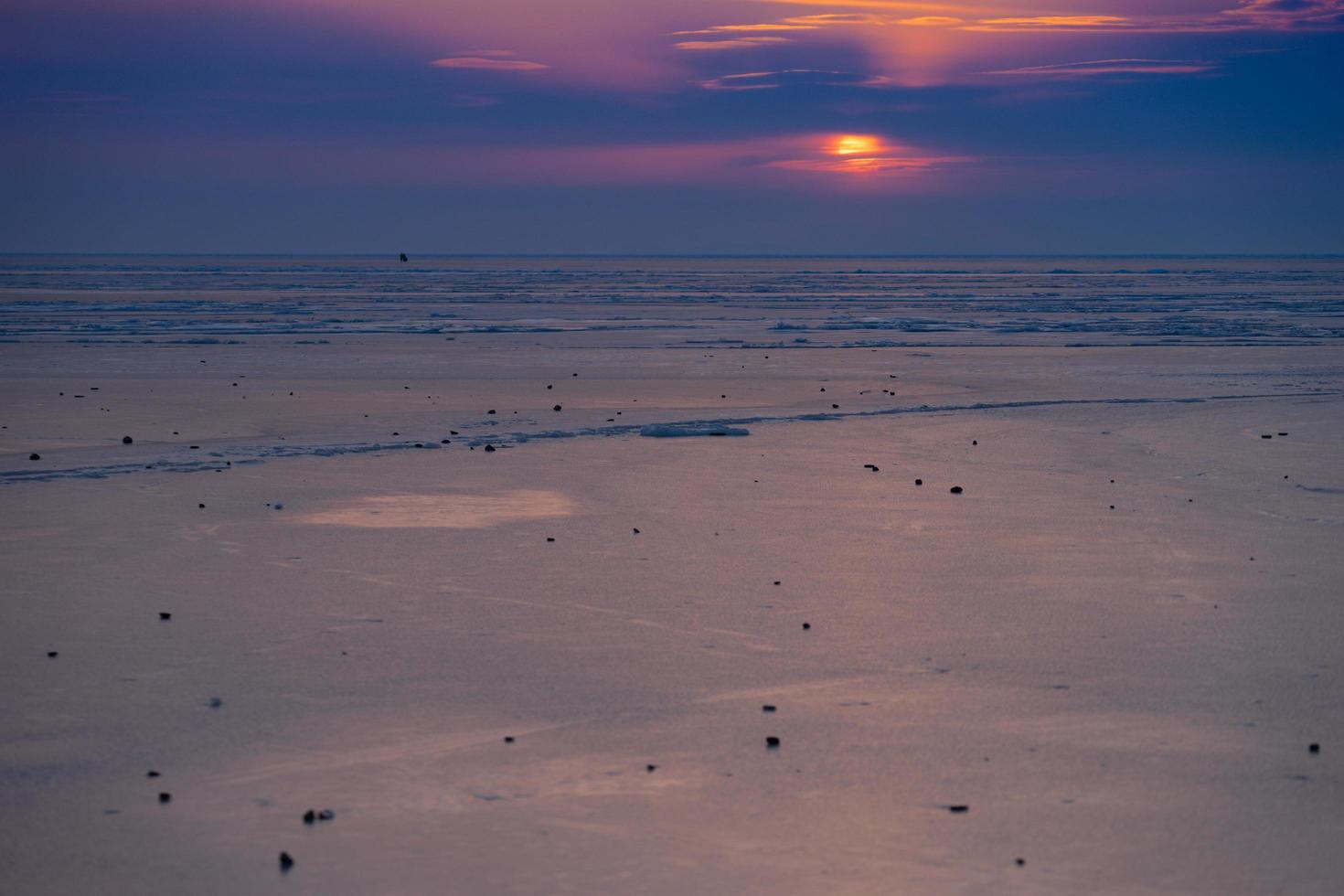 kleurrijke bewolkte zonsondergang over een strand bij amoerbaai in vladivostok, Rusland foto