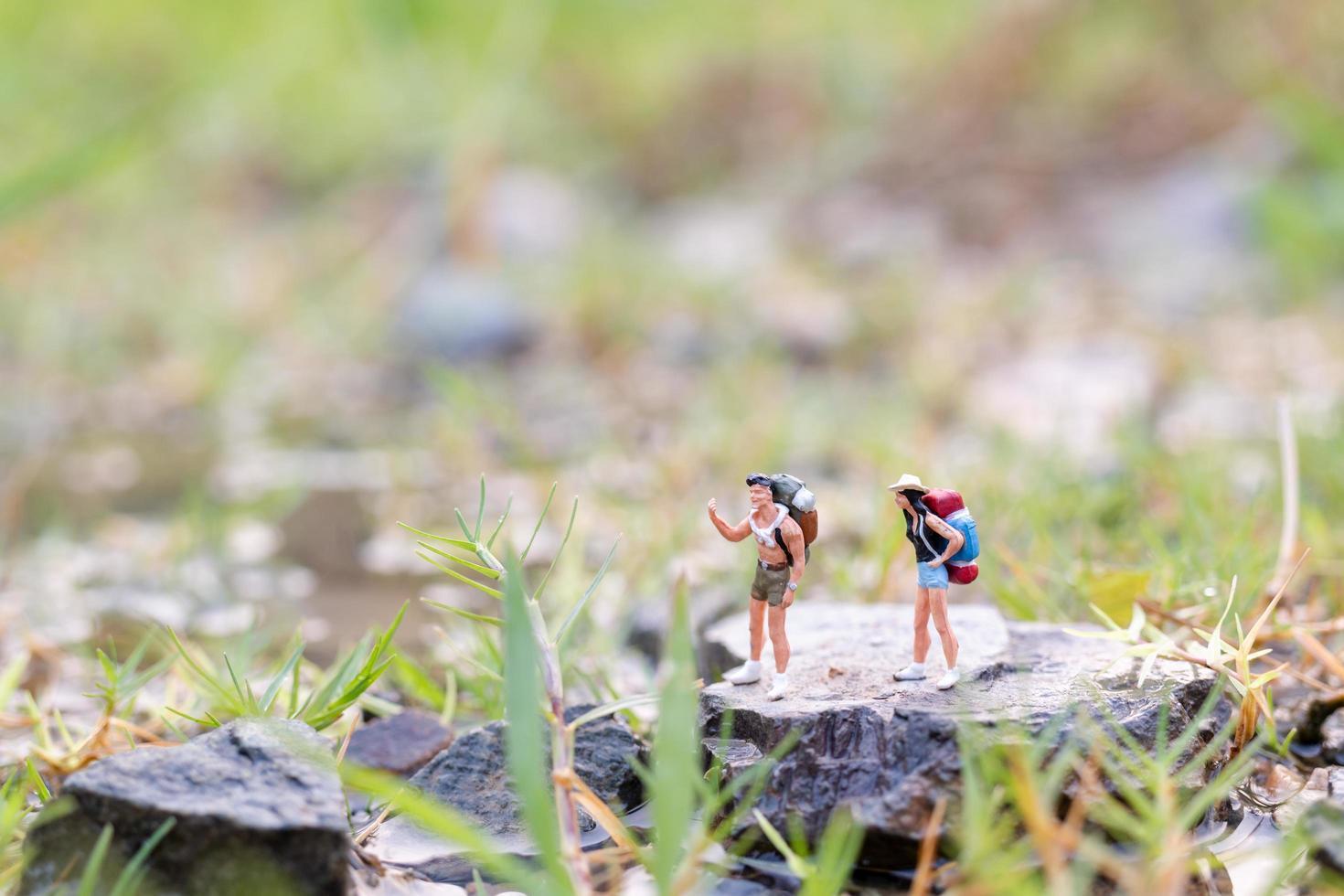 miniatuurreiziger met rugzakken die in het veld-, reis- en avontuurconcept lopen foto