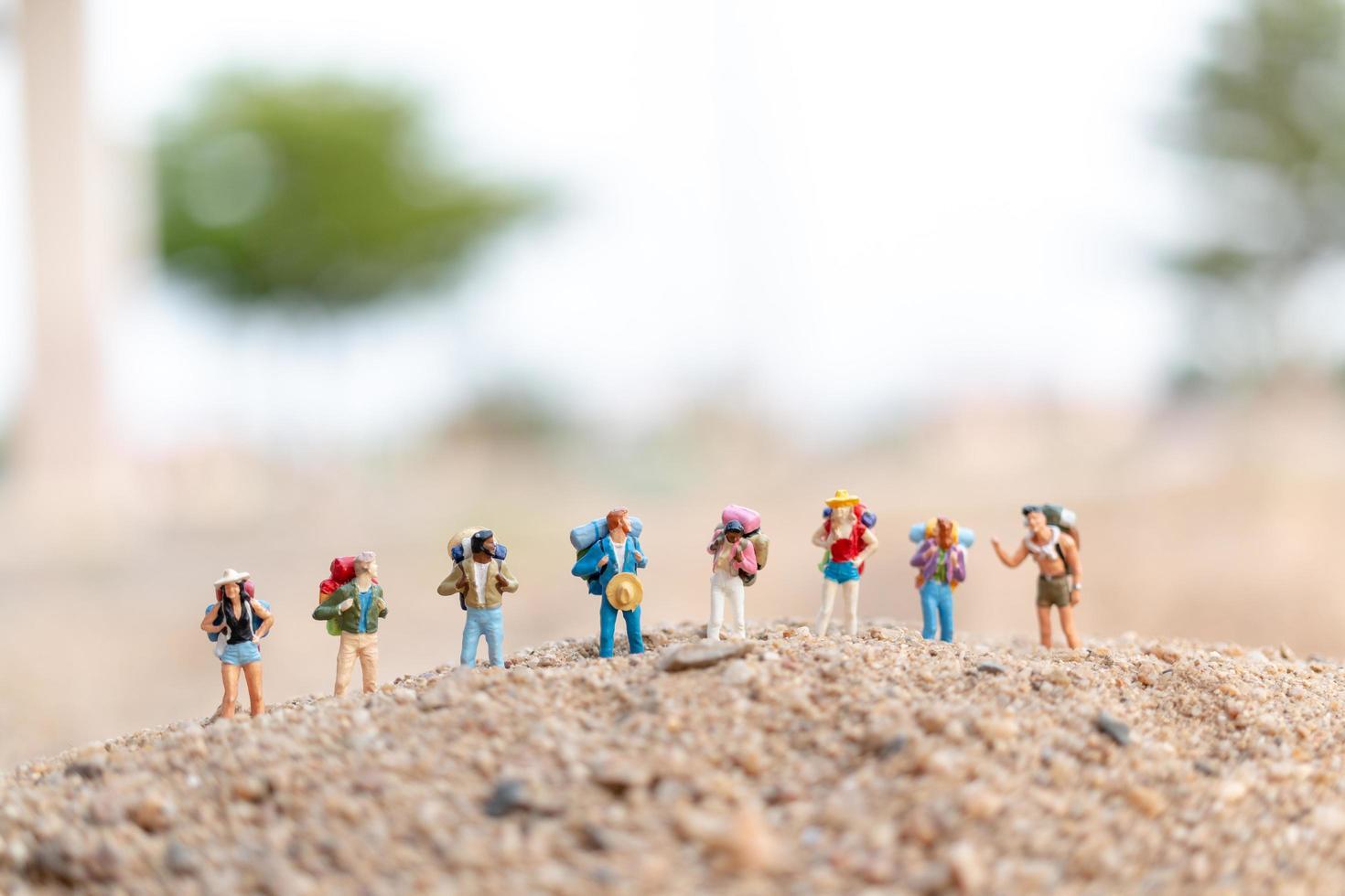 miniatuurreizigers met rugzakken die op zand, reis en avontuurconcept lopen foto