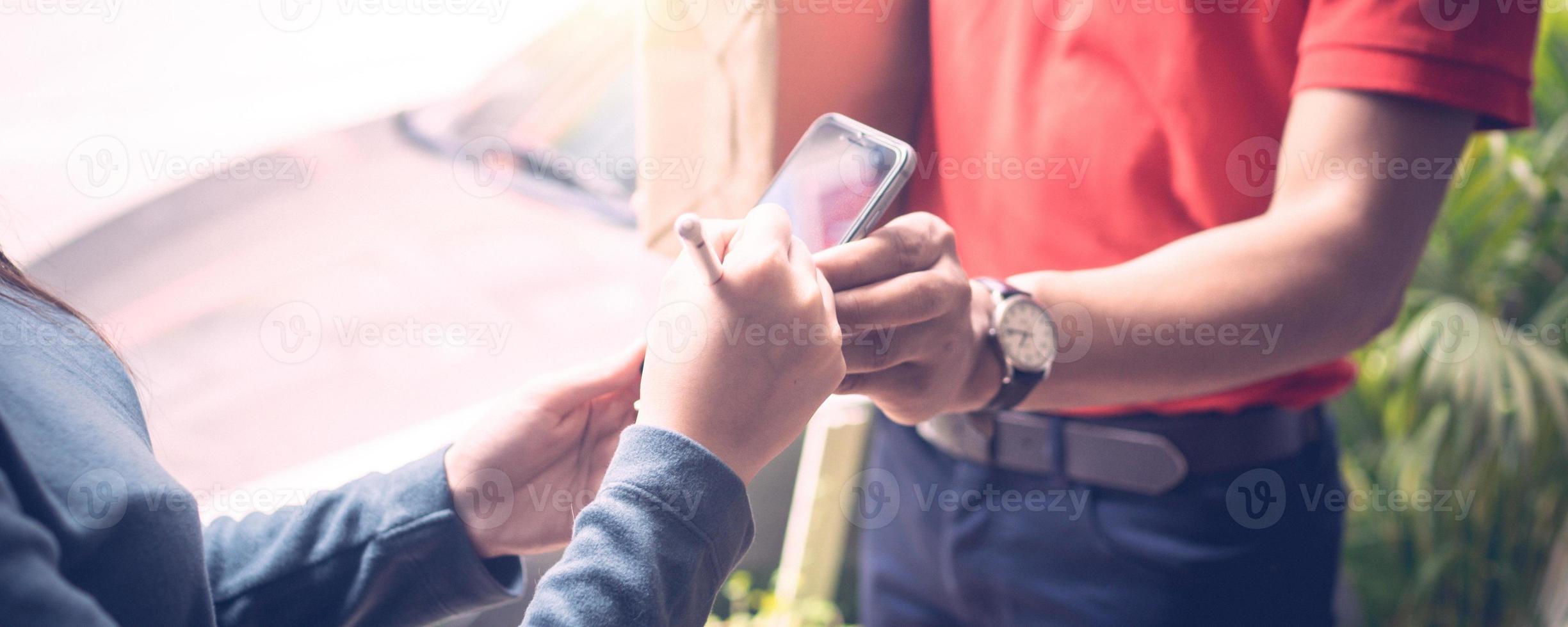 persoon die een mobiele telefoon ondertekent die wordt vastgehouden door een bezorger foto