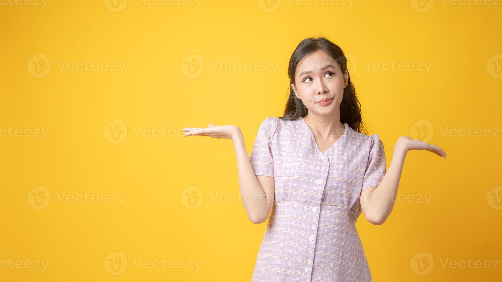 Aziatische vrouw gebaren met beide handpalmen omhoog op gele achtergrond foto