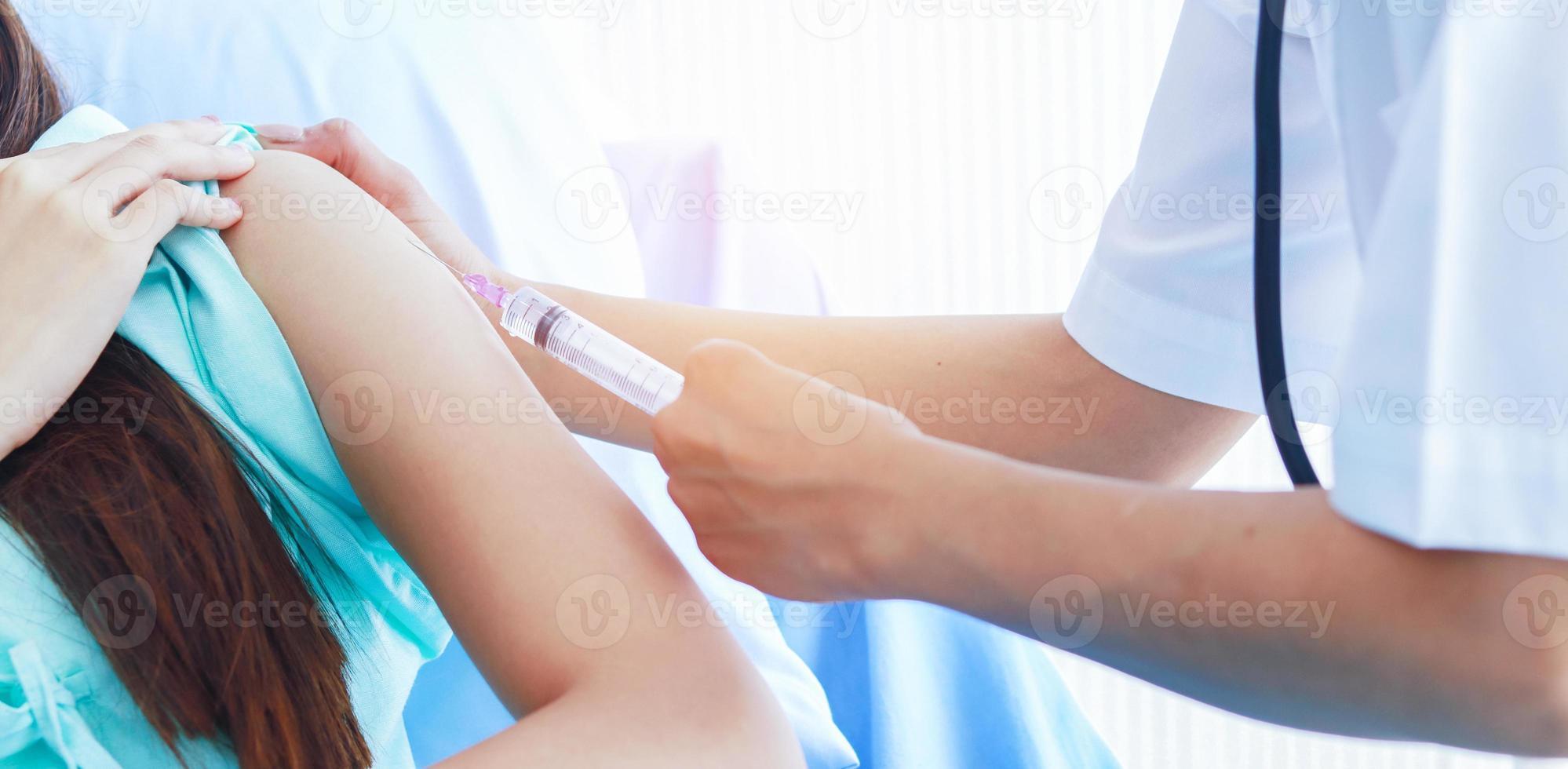 vrouwelijke arts die een spuit in een patiënt injecteert foto
