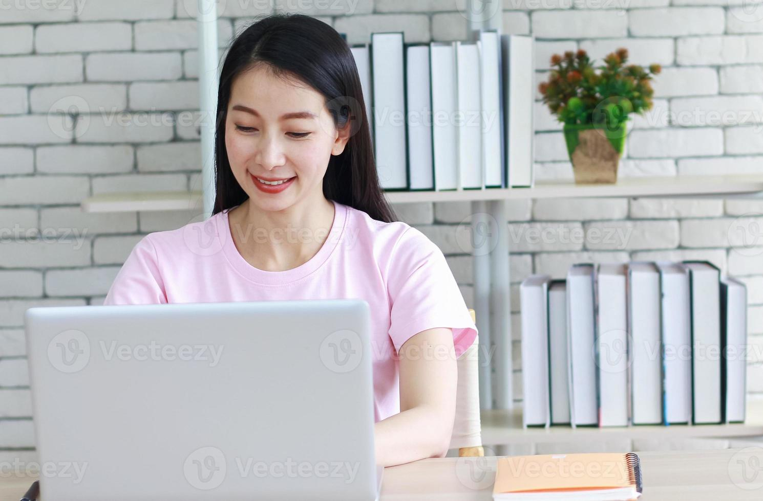 Aziatische vrouw lezen en huiswerk doen foto