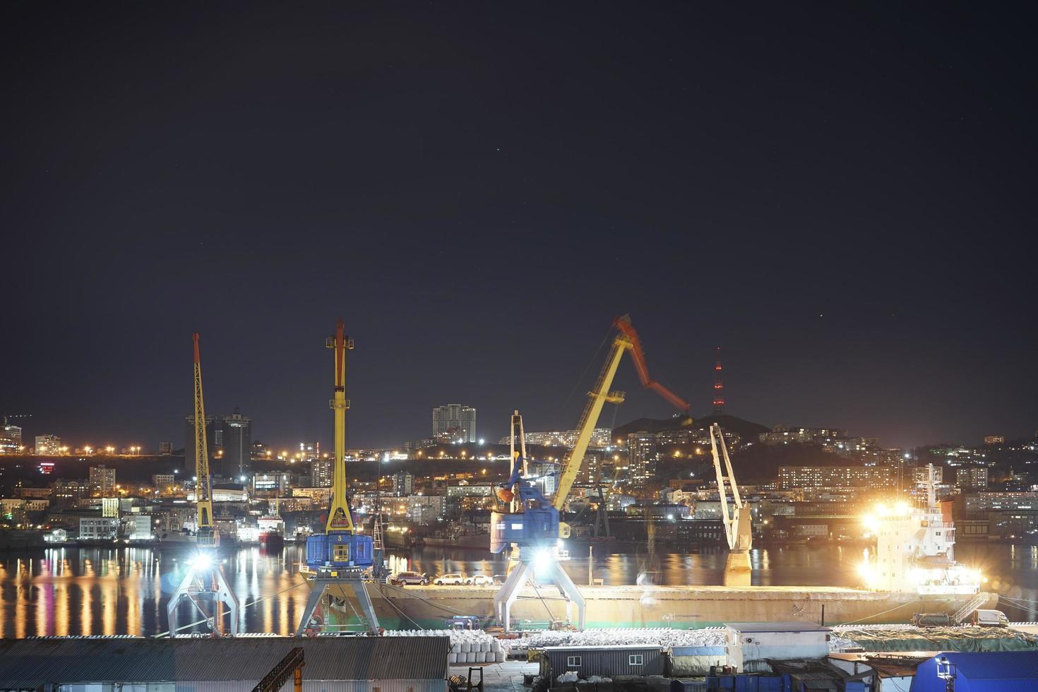 nacht stadslandschap met uitzicht op een haven en skyline op de achtergrond in Vladivostok, Rusland foto