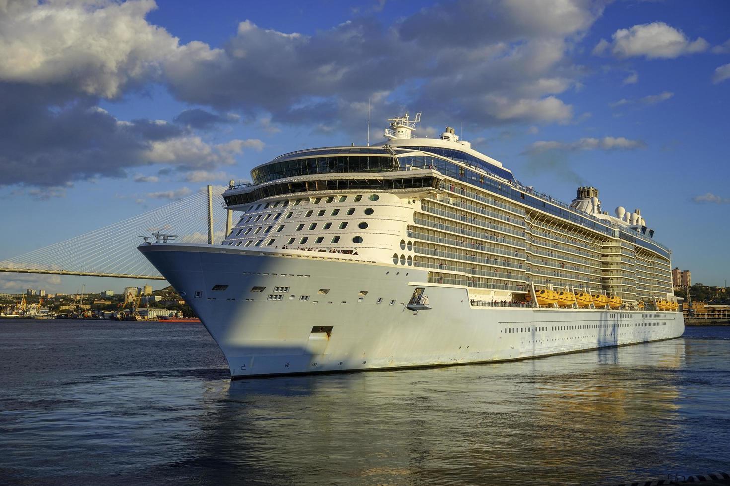 cruiseschip in amoerbaai naast gouden brug in vladivostok, rusland foto