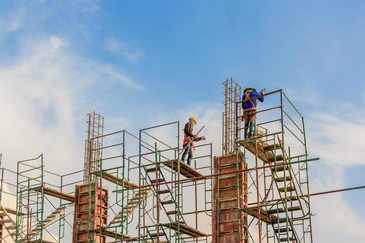 bouwvakkers werken op steigers op een hoog niveau door gestelde veiligheidsnormen foto