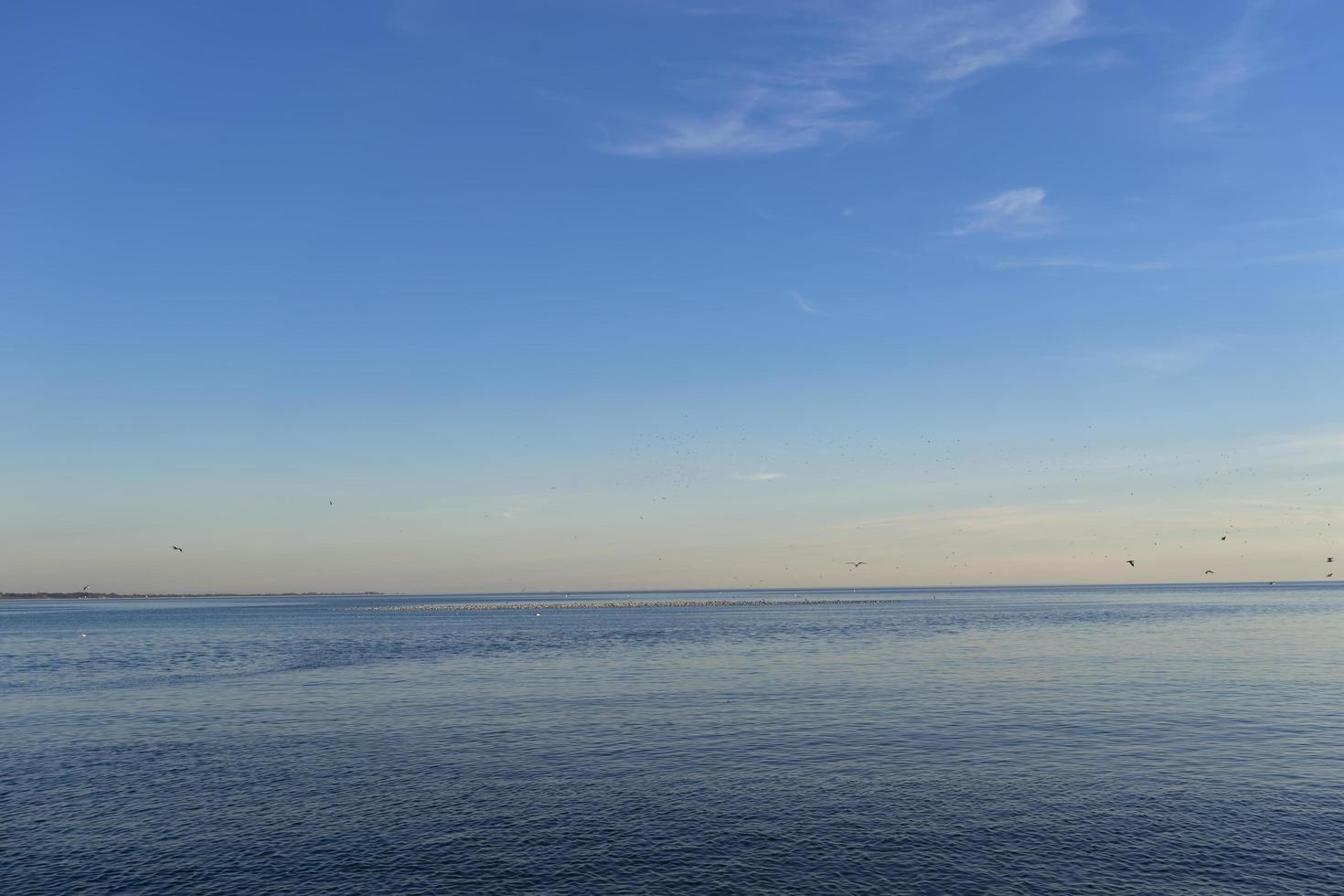 zeegezicht van een watermassa met kleurrijke horizon en blauwe hemel foto