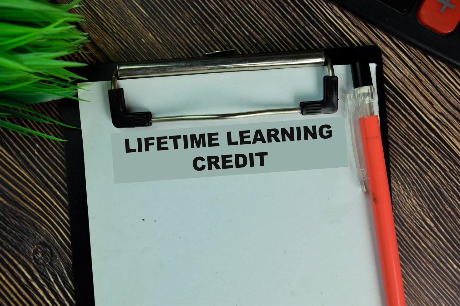 levenslange leerkrediet geschreven op papierwerk geïsoleerd op een houten tafel foto