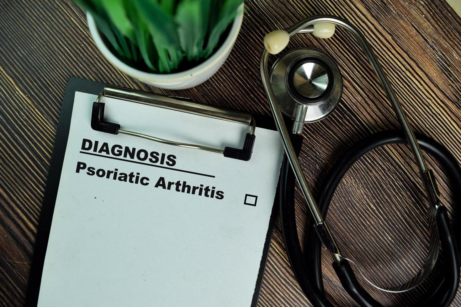 diagnose - artritis psoriatica geschreven op papierwerk geïsoleerd op een houten tafel foto