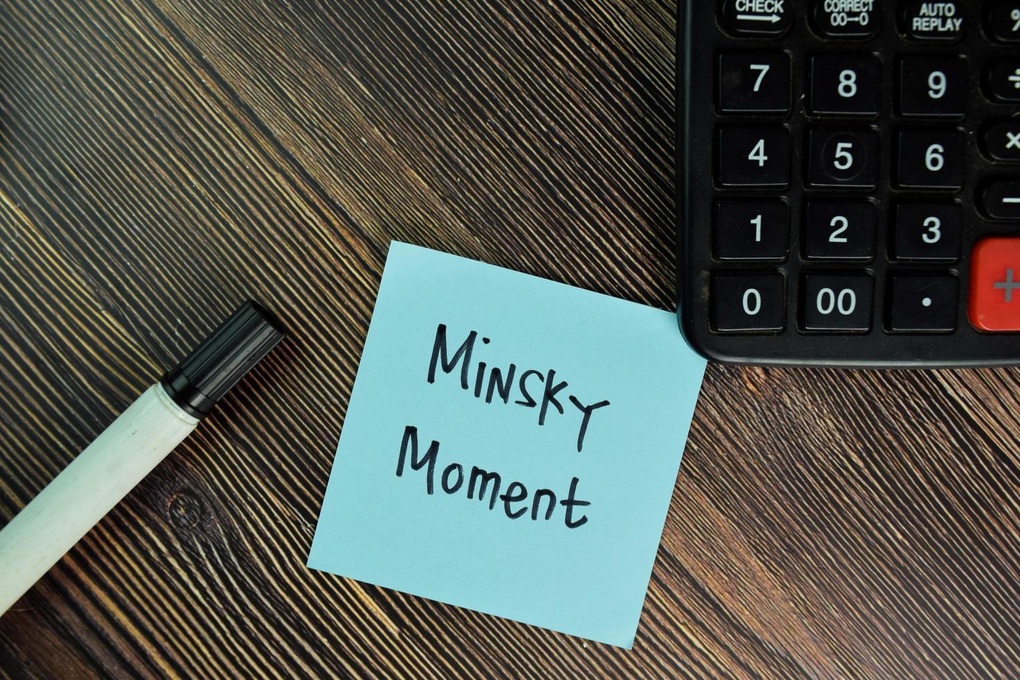 minsky moment geschreven op notitie geïsoleerd op houten tafel foto