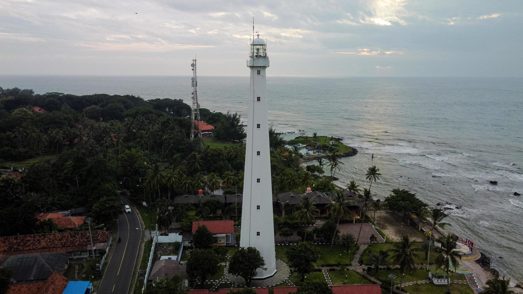 Banten, Indonesië 2021 - luchtfoto van het landschap van de zonsondergang op de rotsen van de vuurtoren op zee foto