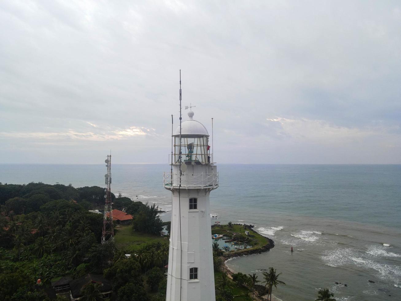 Banten, Indonesië 2021 - luchtfoto van de zeehaven van Pelabuhan Merak en het stadshaveneiland Luchtfoto van het landschap van de zonsondergang op de rotsen van de vuurtoren op zee. zonsondergang vuurtoren scène. op elk strand met lawaaiwolk en stadsgezicht. Banten, Indonesië, 3 maart 2021 foto
