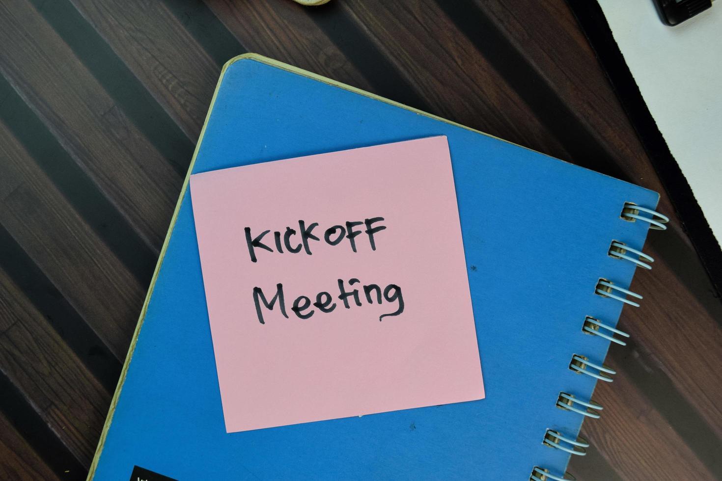 kickoff meeting geschreven op notitie geïsoleerd op een houten tafel foto