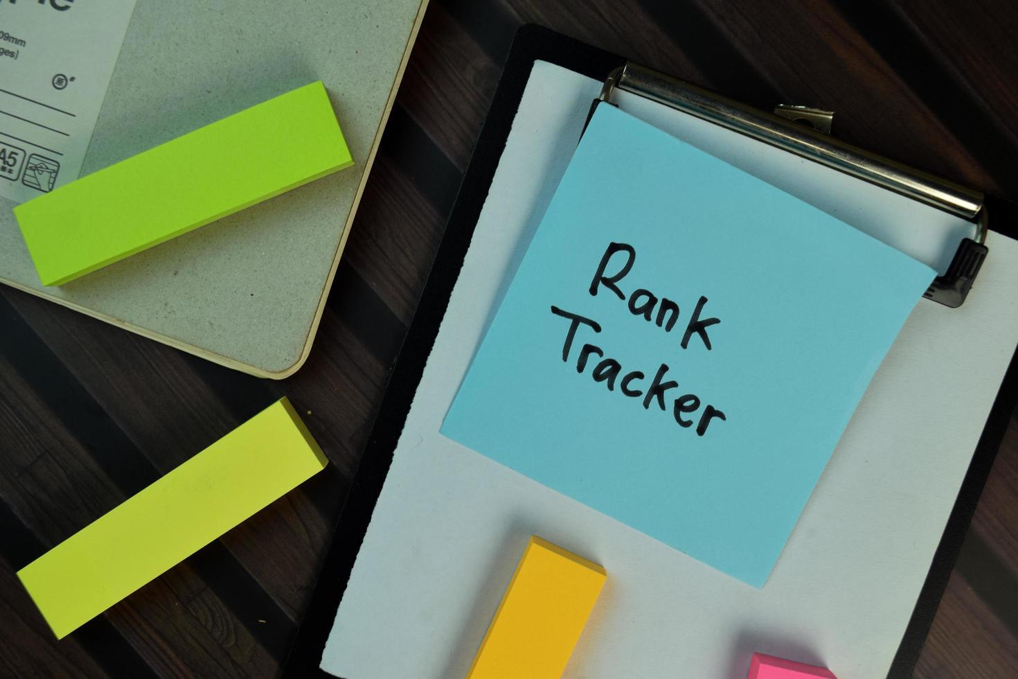 rang tracker geschreven op notitie geïsoleerd op houten tafel foto
