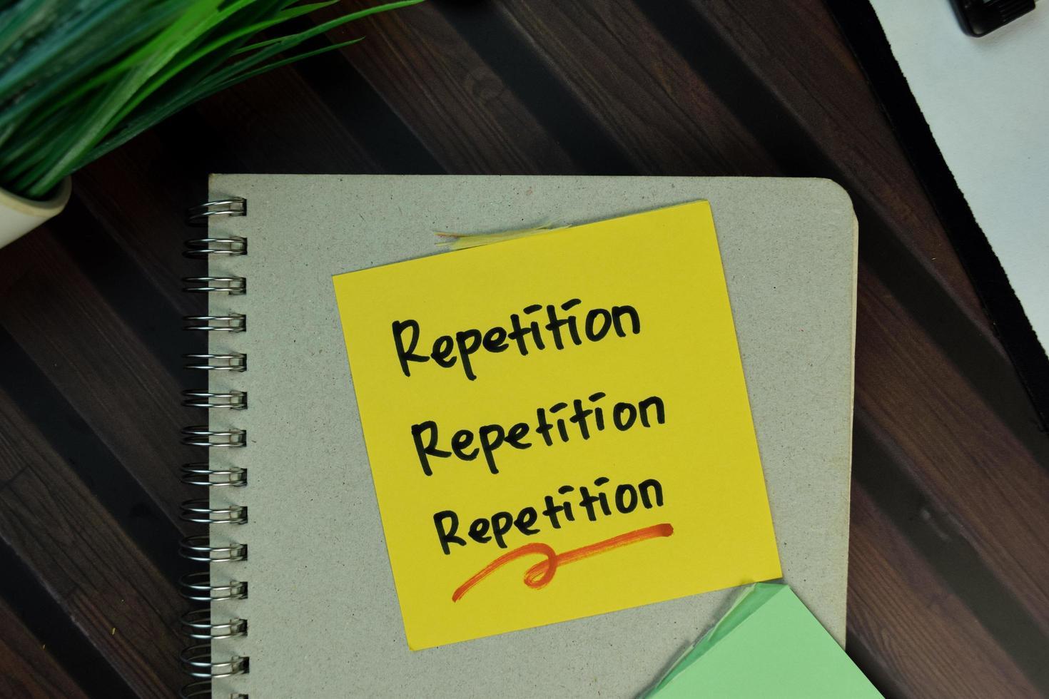herhaling, herhaling, herhaling geschreven op notitie geïsoleerd op houten tafel foto