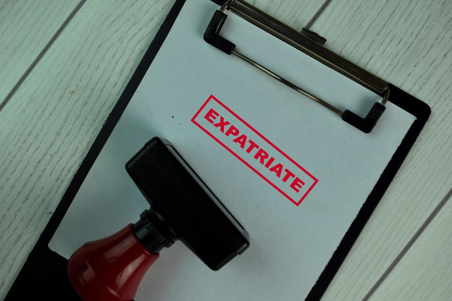 rode handvat rubberen stamper en expat tekst geïsoleerd op tafel foto