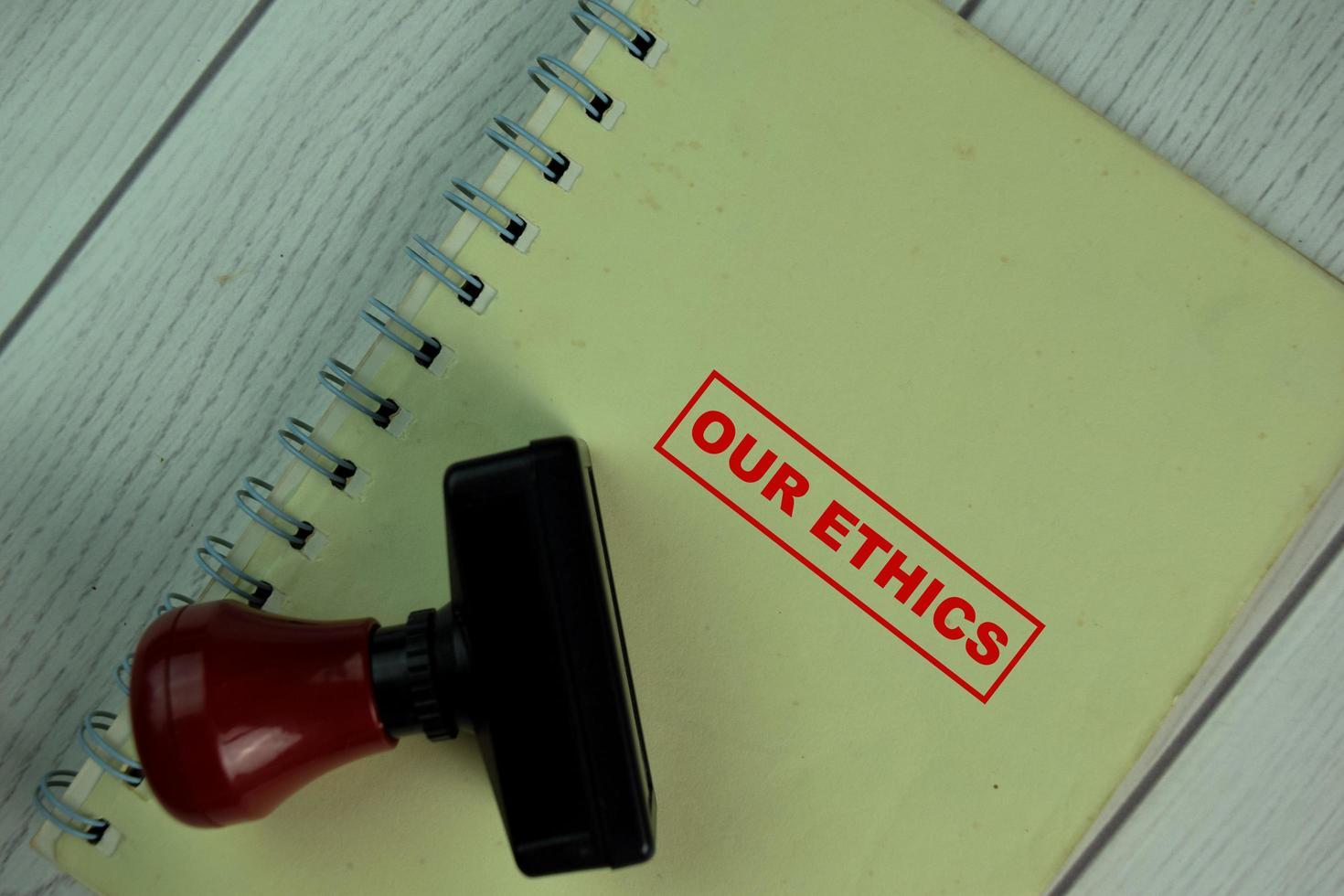 rode handvat rubberen stamper en onze ethische tekst geïsoleerd op tafel foto