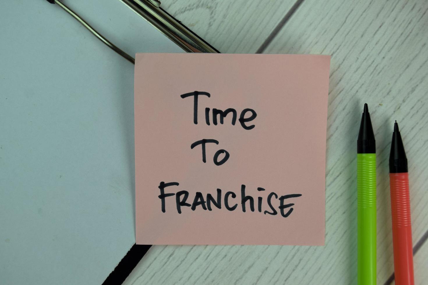 tijd om franchise geschreven op notitie geïsoleerd op houten tafel foto