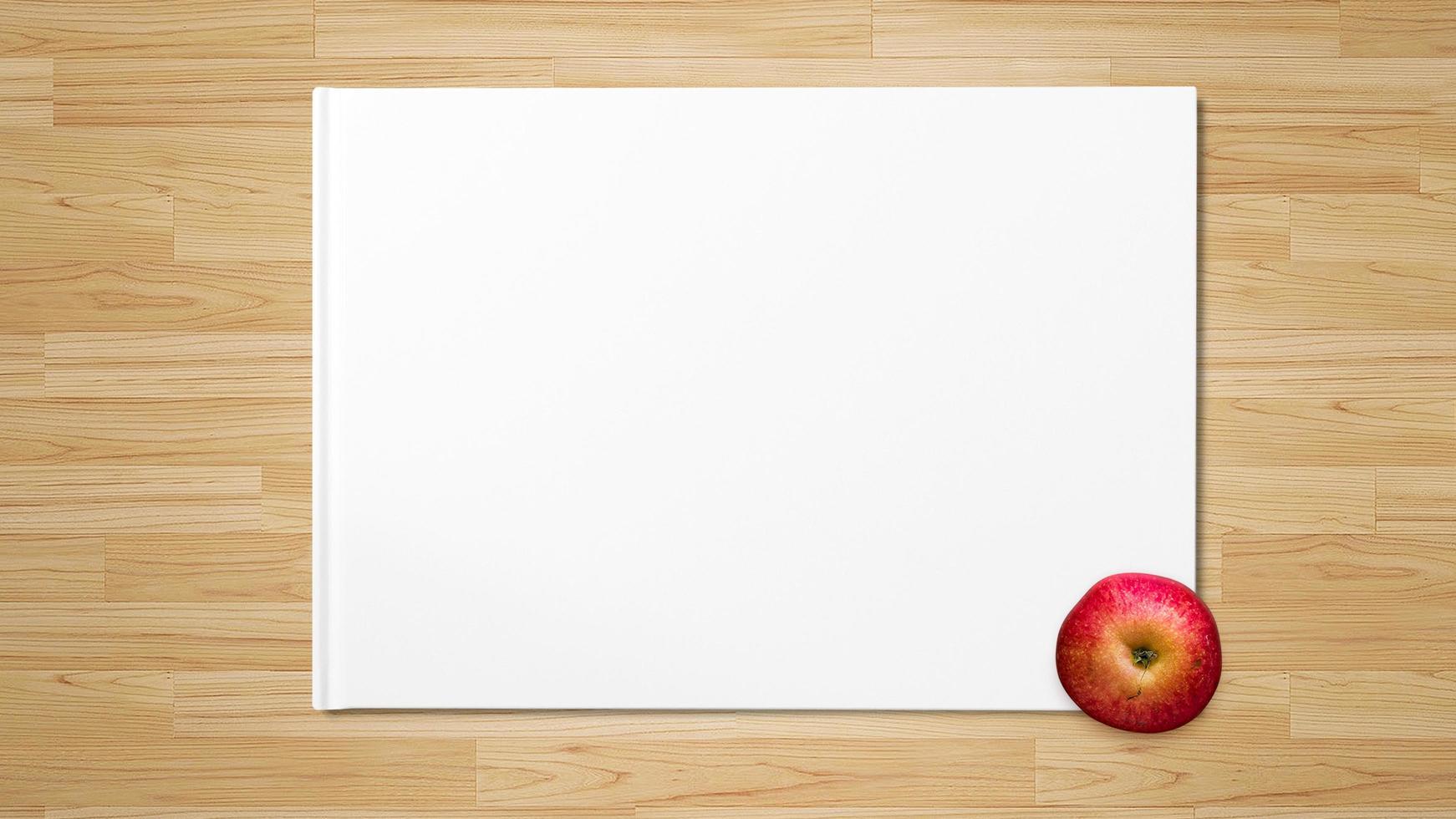 rode appel op wit papier op houten achtergrond foto