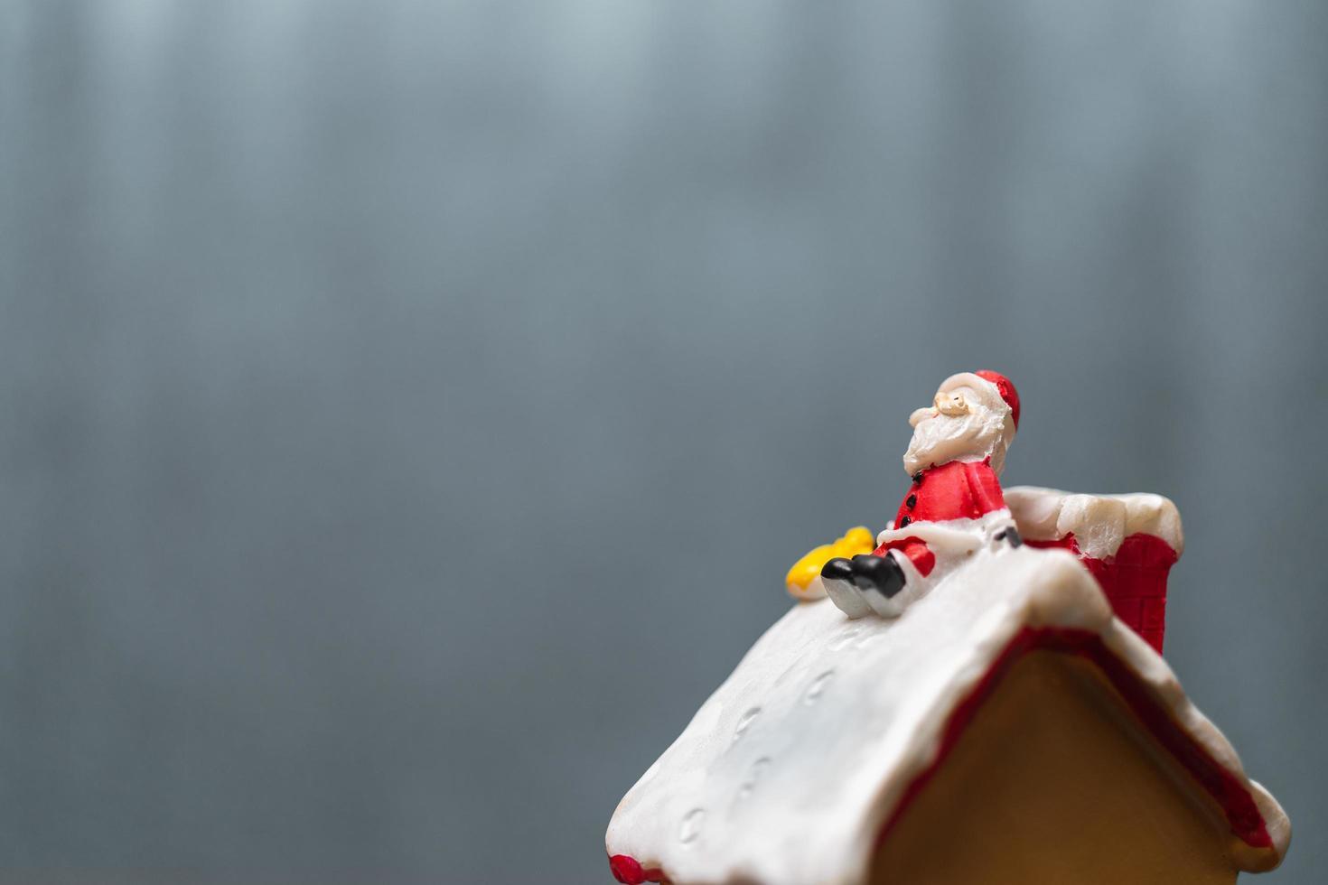 miniatuur kerstman zittend op een dak, kerstlegende en prettige vakantie concept foto