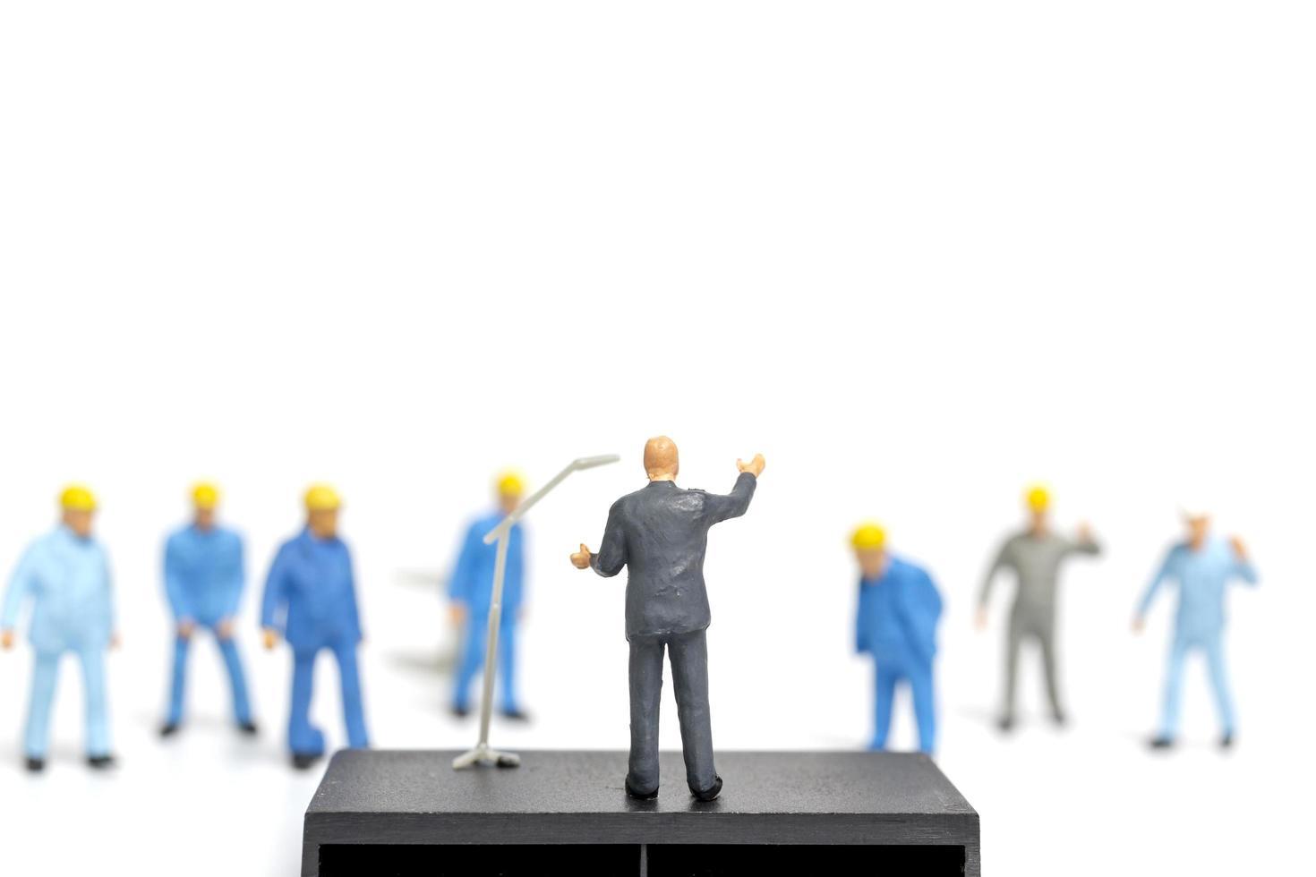 miniatuurmensen die luisteren naar een politicus die spreekt tijdens een verkiezingsbijeenkomst foto