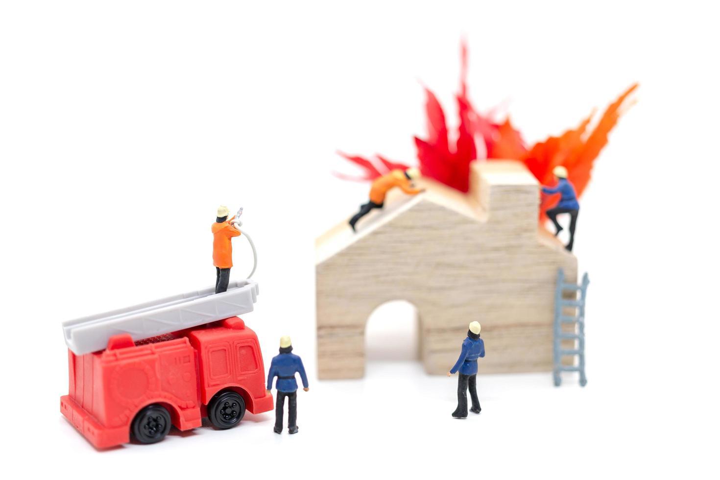 miniatuurbrandweerlieden die zorgen voor een brandnoodsituatie in een houten huis foto