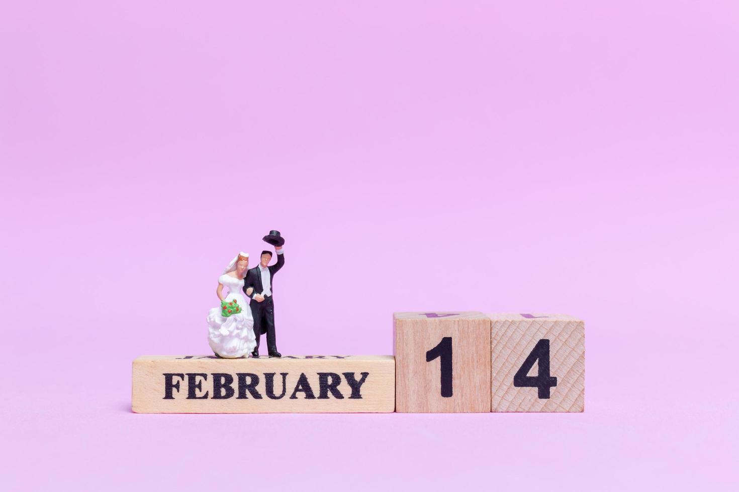 miniatuur bruid en bruidegom op een roze achtergrond, Valentijnsdag en huwelijksconcept foto
