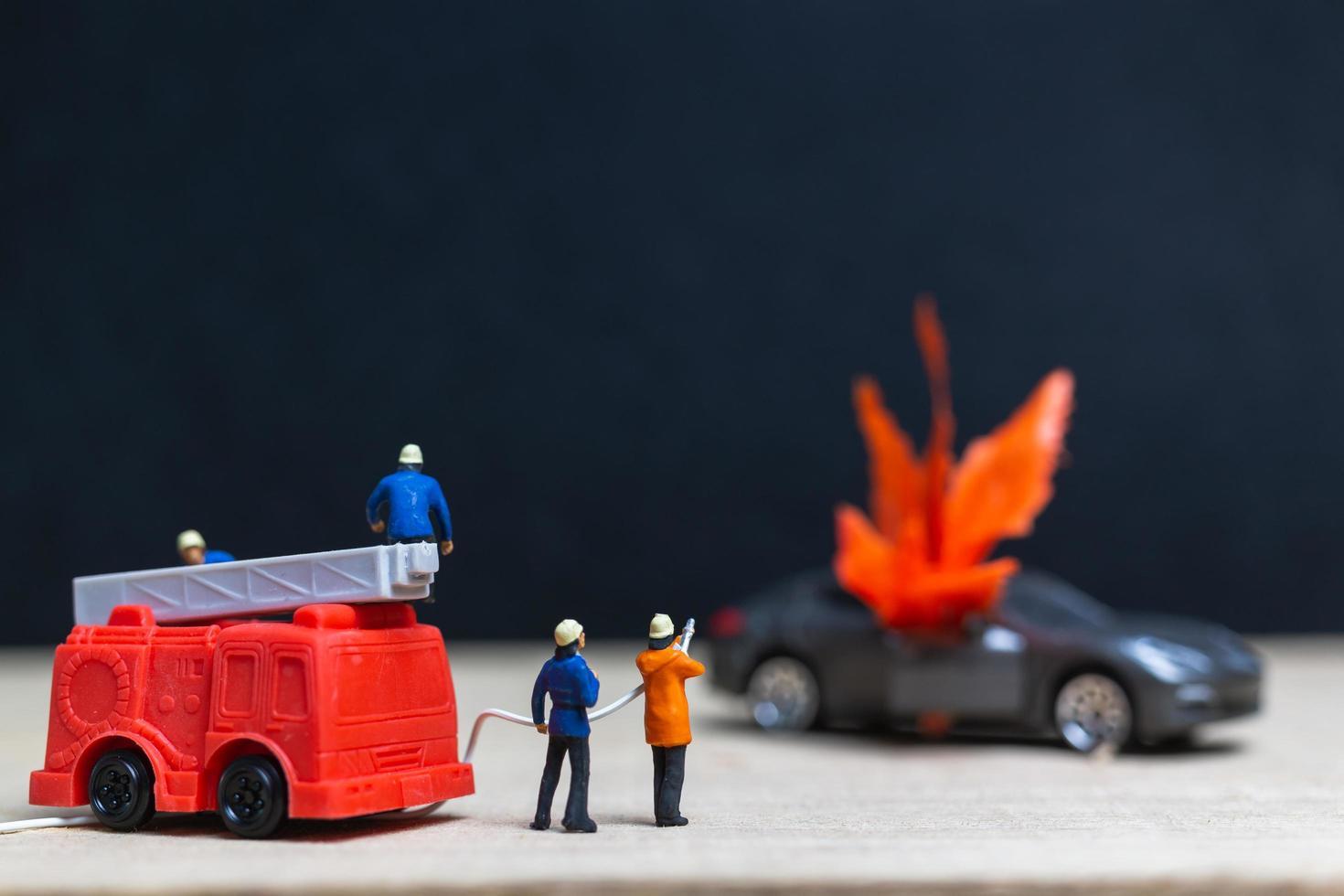 miniatuurbrandweerlieden bij een auto-ongeluk, auto-ongelukconcept foto