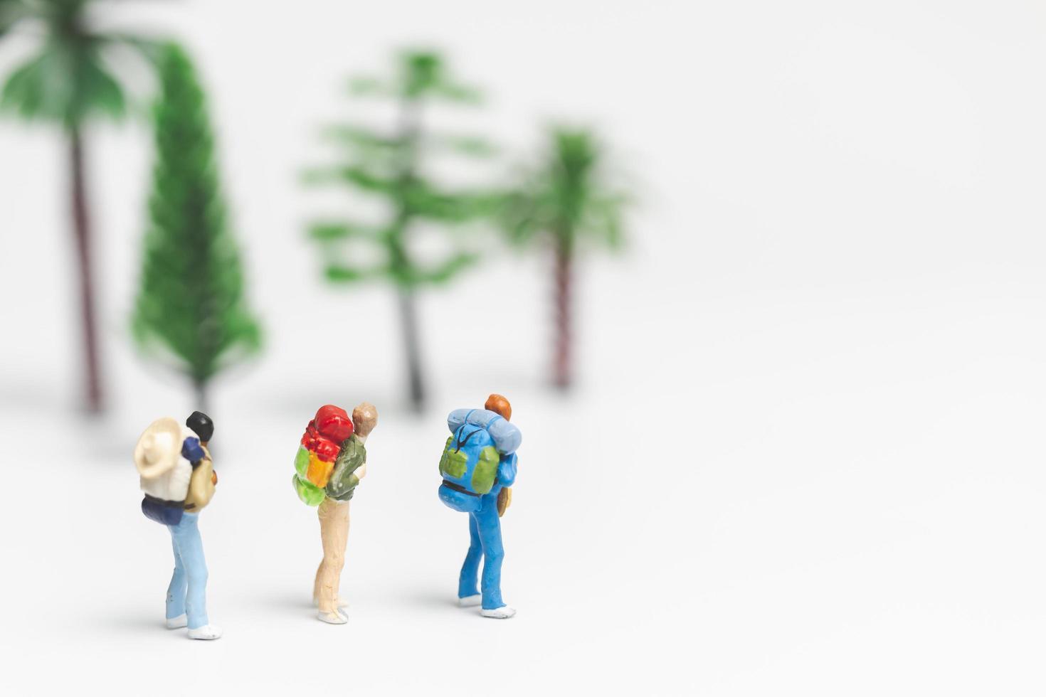 miniatuurreizigers met rugzakken die op een witte achtergrond, reis en avontuurconcept lopen foto