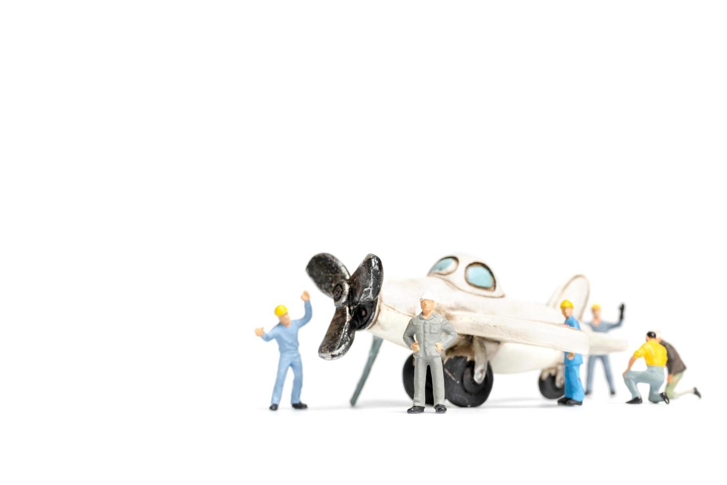 miniatuurarbeiders die een stuk speelgoed vliegtuig op een witte achtergrond herstellen foto