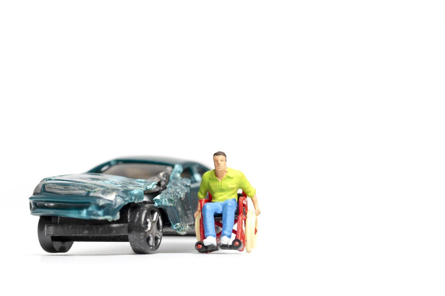 miniatuur man in een rolstoel bij een autowrak op een witte achtergrond foto