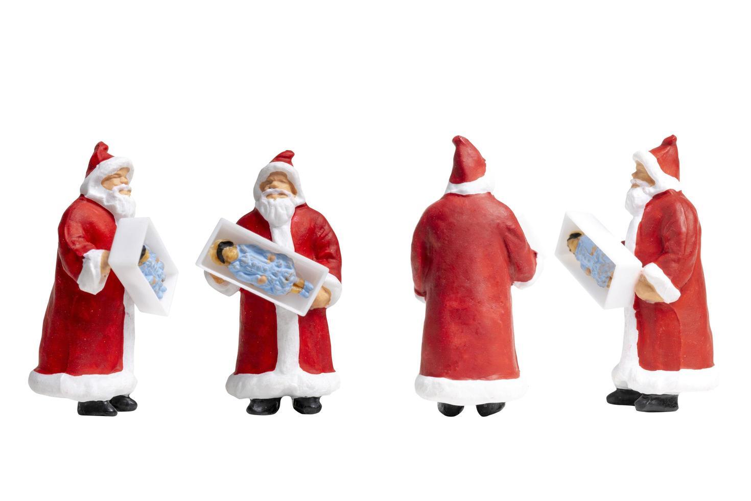 miniatuur kerstman met een geschenkdoos geïsoleerd op een witte achtergrond foto