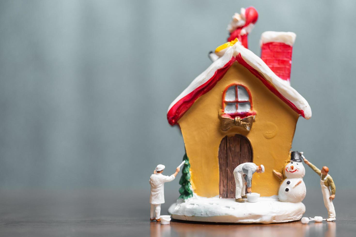 miniatuurmensen die een huis schilderen en de kerstman zittend op het dak, prettige kerstdagen en een fijne vakantie concept foto