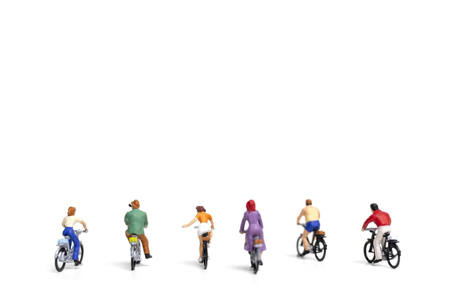 miniatuurvrienden die fietsen berijden die op een witte achtergrond, reisconcept worden geïsoleerd foto