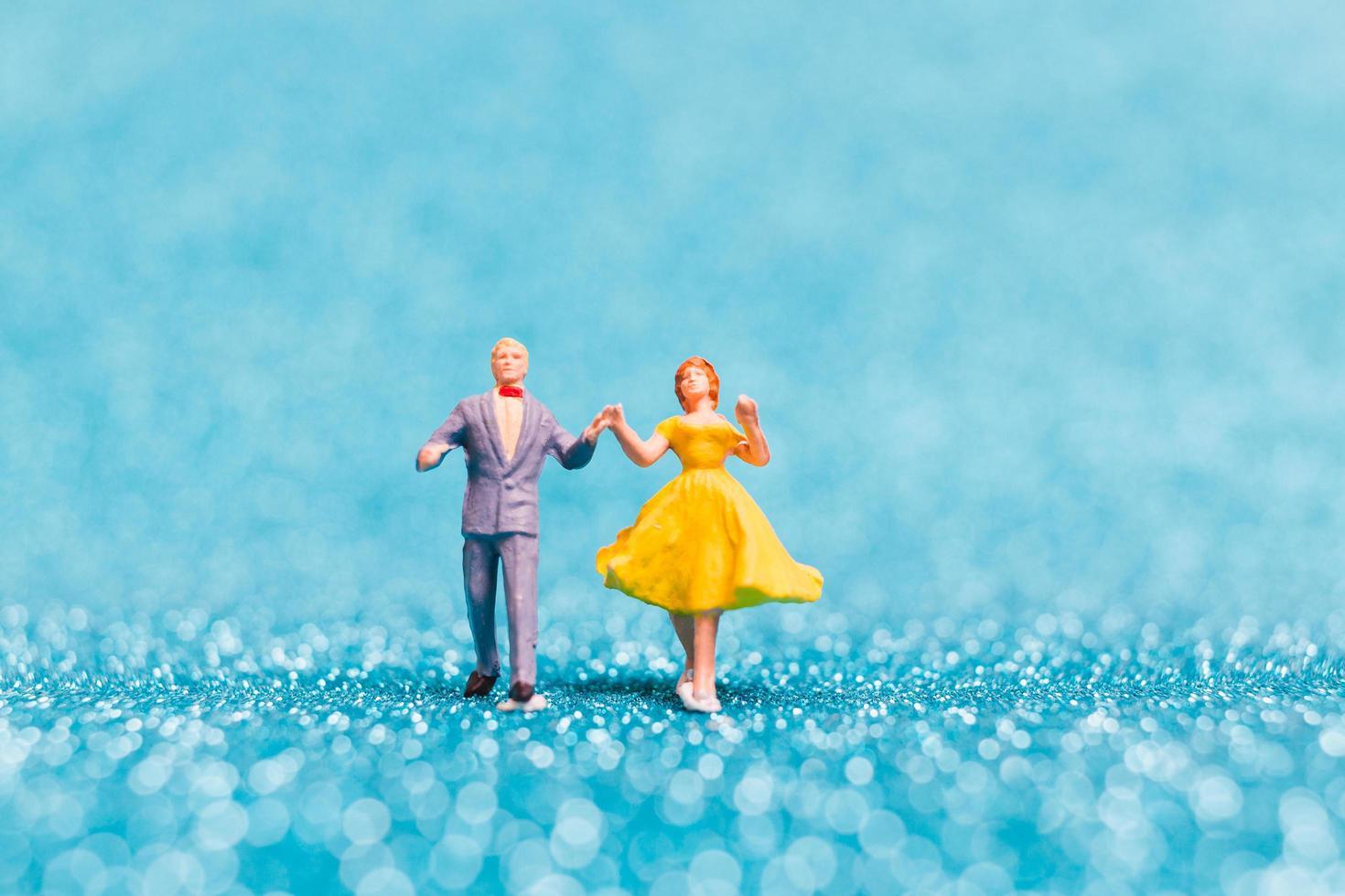 miniatuurpaar dansen op blauwe glitter achtergrond, Valentijnsdag concept foto