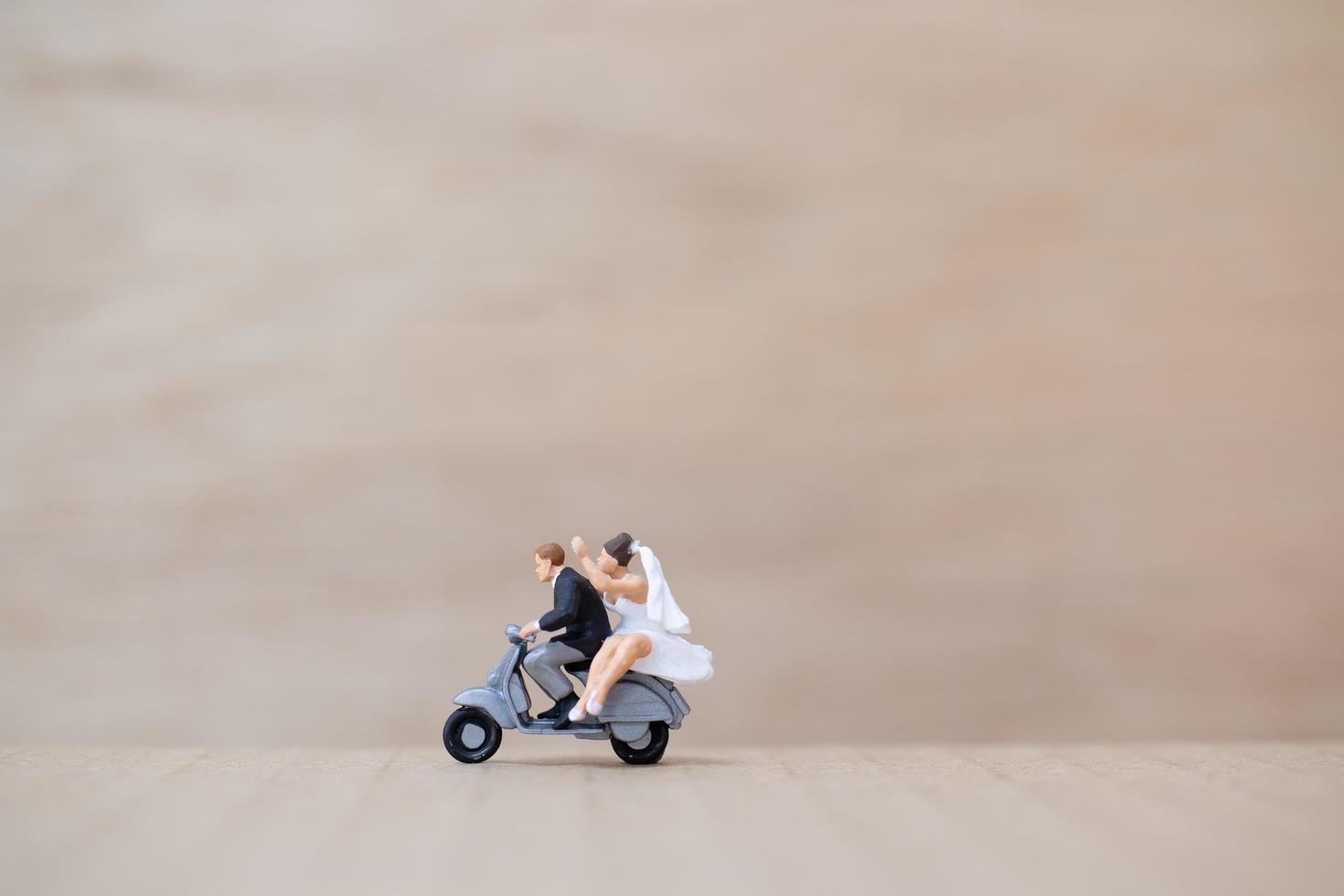 miniatuur bruid en bruidegom op een houten achtergrond foto