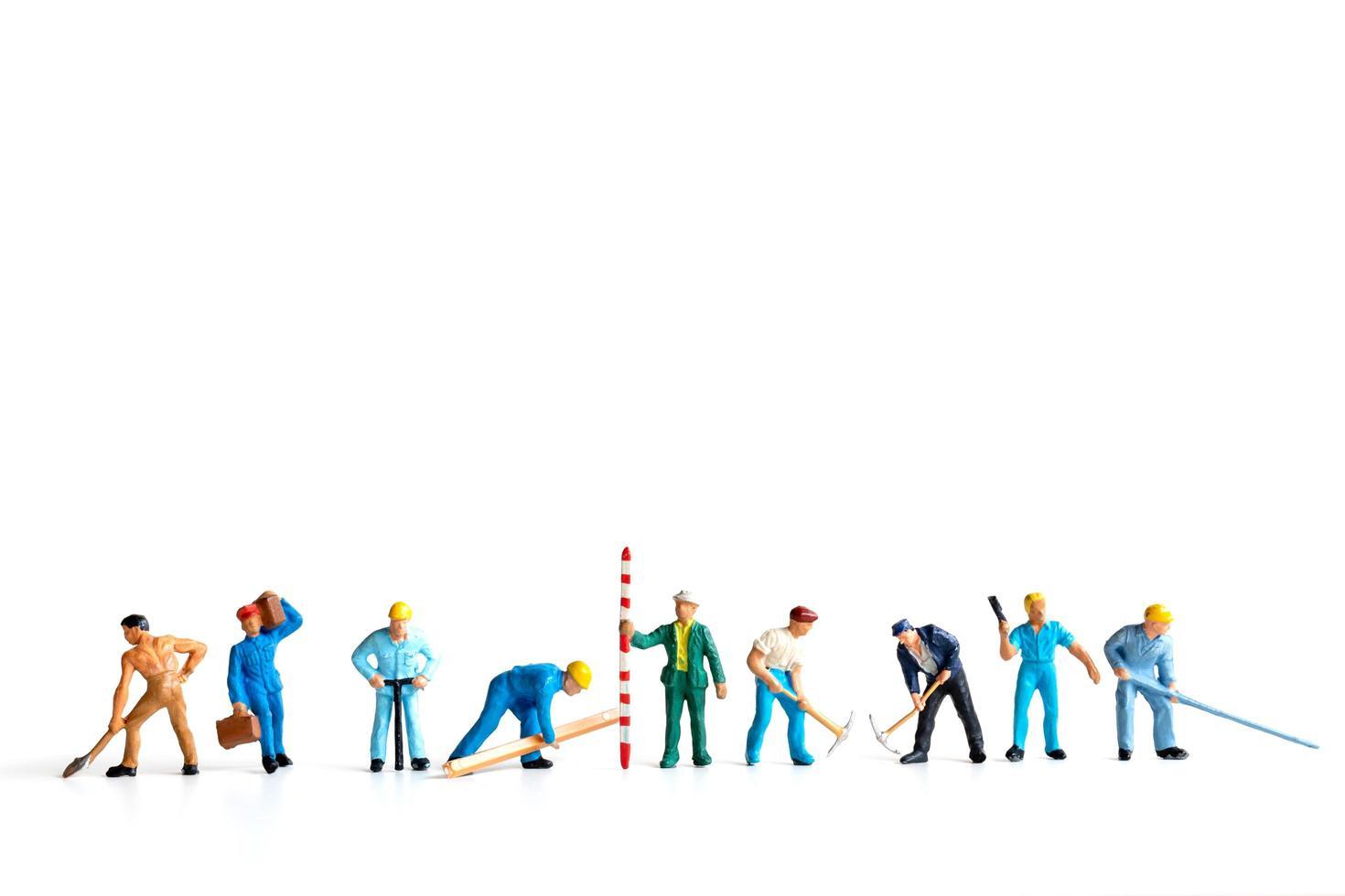 miniatuurarbeiders die zich op een witte achtergrond, arbeidsconcept bevinden foto